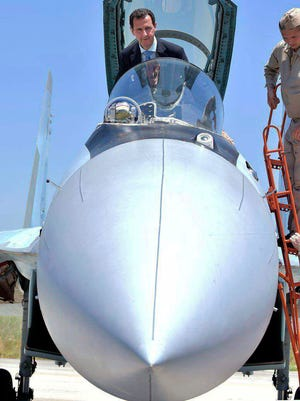 In this June 27, 2017, photo released on the official Facebook page of the Syrian Presidency, Syrian President Bashar Assad climbs into the cockpit of a Russian SU-35 fighter jet as he inspects the Russian Hmeimim air base in the province of Latakia, Syria.