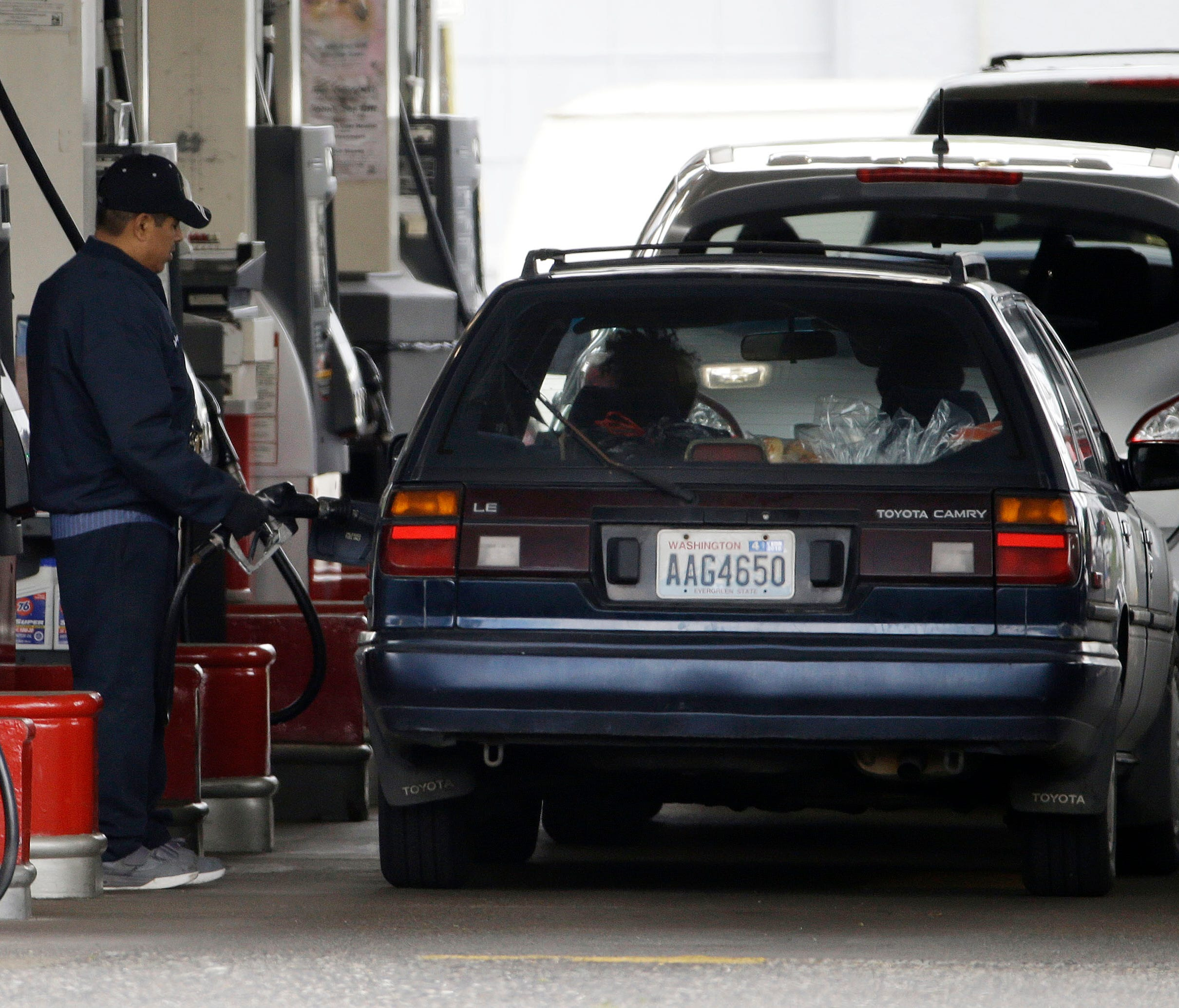 Cars line up May 6, 2015, as an attendant pumps gas at a station in Portland, Ore. AAA projects 41.5 million people will travel for the Memorial Day holiday, despite higher gas prices.