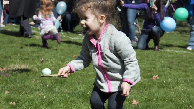 Theia Tucker, of Fremont, smiles while carrying an egg. Hundreds of children participated in the 2016 Easter Egg Roll at Spiegel Grove, home of the Rutherford B. Hayes Presidential Library and Museums.