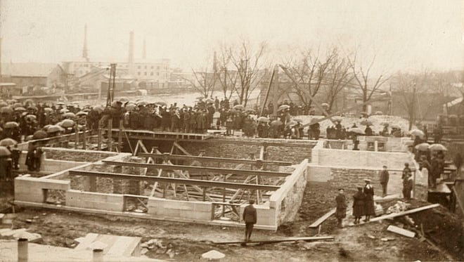 This March 1898 photograph shows the laying of the cornerstone of the Elisha D. Smith Public Library in Menasha. The canal can be seen in the background.