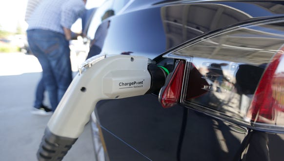 A Tesla electric car charges while on display on Saturday,