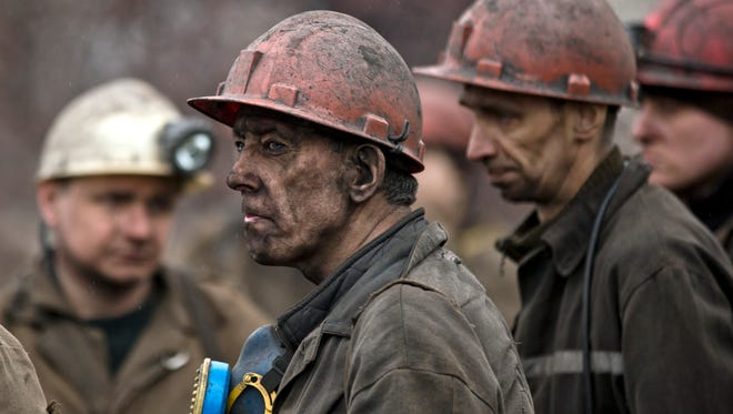 Ukrainian coal miners wait for a bus after returning to the surface of the Zasyadko mine in Donetsk, Ukraine, on March 4, 2015.