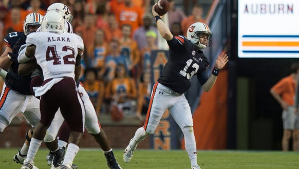 Auburn quarterback Sean White (13) throws during the