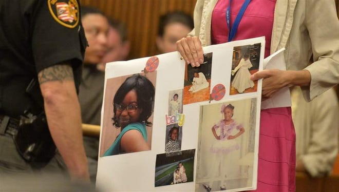 A court worker holds a board of photos of Shirellda Terry, a victim of Ohio serial killer Michael Madison, who received a death sentence last month. Some victims of crime and their families say talking with offenders helps them come to terms with what happened.