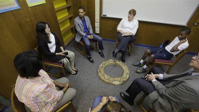 A group of seventh-graders sit in a restorative justice circle to talk out a conflict at school. States are increasingly pushing to bring the practice into the criminal justice system as a way for both juveniles and adults to avoid prison time.
