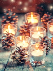 Glowing small candles and fir cones on an old wooden background.