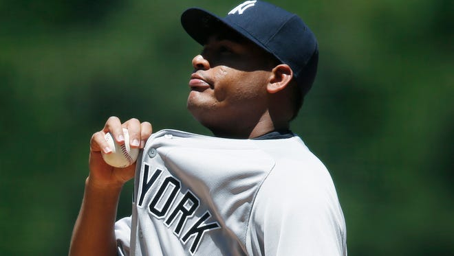 New York Yankees starting pitcher Ivan Nova tries to cool off between pitches as the temperatures soars into the mid-90s while facing the Colorado Rockies in the first inning of a baseball game Wednesday, June 15, 2016, in Denver.