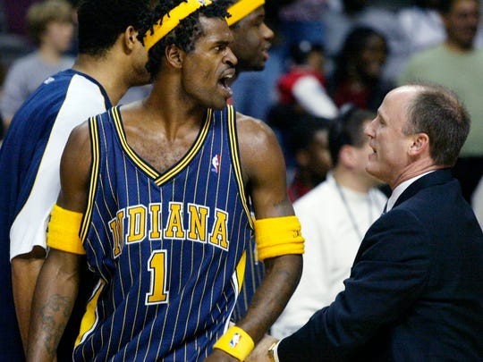 Indiana Pacers' Stephen Jackson (1) is escorted off the court by  following their fight with the Detroit Pistons and fans Friday, Nov. 19, 2004, in Auburn Hills, Mich. (AP Photo/Duane Burleson)