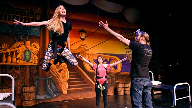 "Jane, played by Courtney Larson, left, lifts into the air after a sprinkling of pixie dust from Peter Pan, played by Grace Knoblach, center, while blocking the scene with Shad Ramsey of ZFX Flying Effects on Tuesday, March 8, at the Paramount Theatre. Actors from St. John's Preparatory School took flying lessons for their upcoming show ""Peter Pan."""