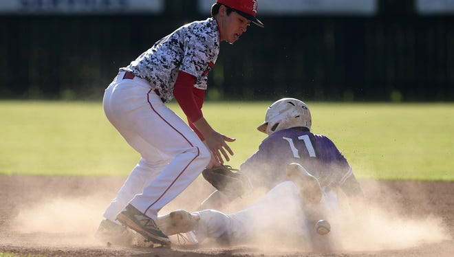 Lexington's Raleigh Odle (13) searches for the ball as Milan's Conner Creasy (11) safely slides into second base at Joyner Field in Milan City Park in Milan, Tenn., on Thursday, April 6, 2017.
