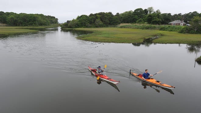 A couple of kayakers paddle down the Swan River in Dennis.