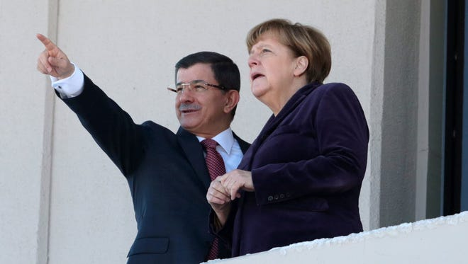 German Chancellor Angela Merkel and Turkish Prime Minister Ahmet Davutoglu speak as they look toward the city center after a welcome ceremony in Ankara, Turkey, on Feb. 8, 2016.