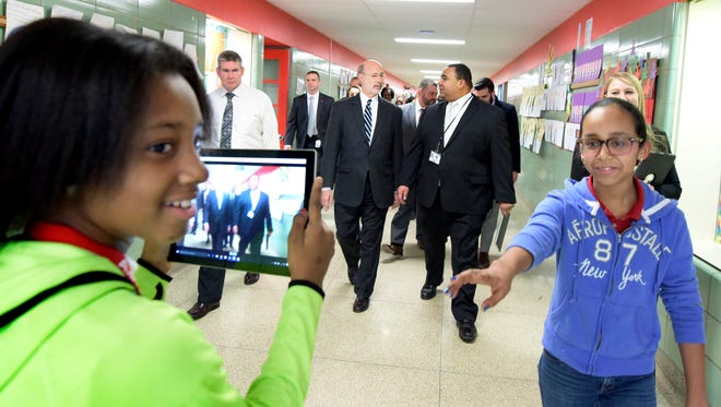 """""""Goode News Crew"""" member Aaliyah Ushry, left, backpedals as she records Governor Tom Wolf's visit to Goode K-8 with co-member Ni'lee Mariche, both sixth-graders, Thursday, Feb. 18, 2016. Wolf, left center, talks with York City School Superintenent Dr. Eric Holmes while touring the school. Bill Kalina photo"""