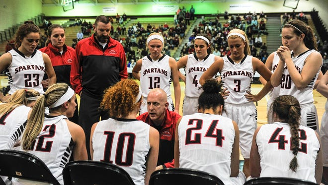 Pleasant girls basketball coach Nate Dendinger, center, talks to his team during a timeout at last week's Division III district championship game at Ohio Dominican. The Spartans will play for a Division III regional title Saturday at 1:30 p.m. at Springfield High School when they face Versailles.