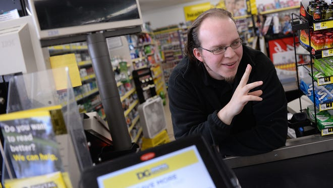Lucas Holliday waves to a customer while posing for a portrait on Tuesday, Nov. 15, 2016 at the Dollar General, 5640 S. Martin Luther King Blvd. in Lansing. A video of Holliday singing behind the cash register went viral.