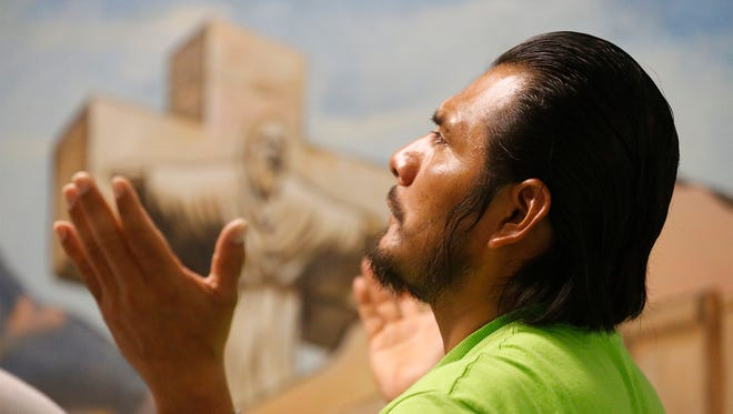 Marco Gomez Lopez prays during Mass on Wednesday morning at the Center of Peace at the Opportunity Center for the Homeless. The center will have a Way of the Cross on Friday in honor of Good Friday.