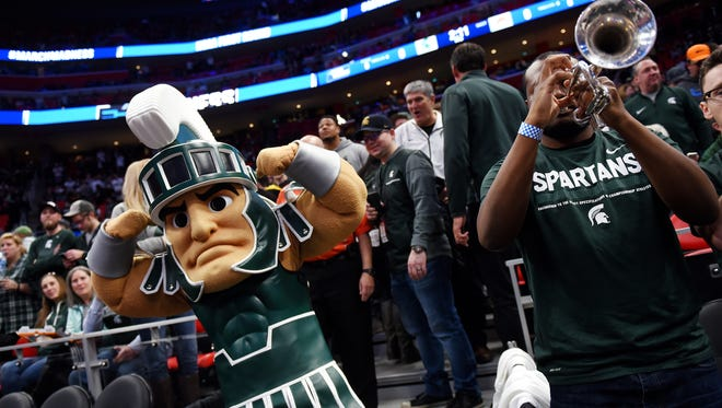 Michigan State mascot Sparty, left, flexes his muscles near the band before the Spartans game against Bucknell on Friday, March 16, 2018, at the Little Caesars Arena in Detroit.