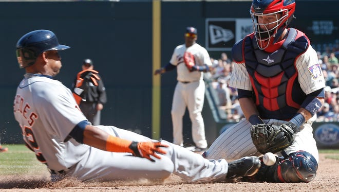 Minnesota Twins catcher Chris Herrmann, left, loses the ball as Detroit Tigers' Yoenis Cespedes scores the go-ahead run in the eighth inning of a baseball game, Wednesday, April 29, 2015, in Minneapolis.