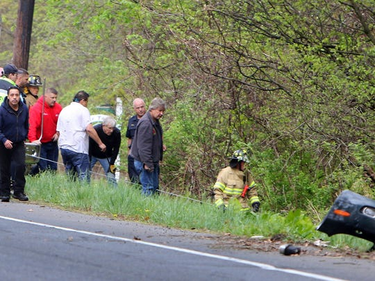 In this May 9, 2017 photo, firefighters try to secure a vehicle that went into a stream during a motor vehicle accident in Woodbury, Conn. Katherine Ann Berman, wife of longtime ESPN broadcaster Chris Berman died in the traffic crash. (Steven Valenti/Republican-American via AP)