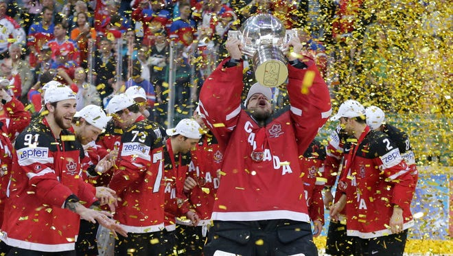 Canada's goalkeeper Mike Smith lifts the trophy after his team defeated Russia in the Hockey World Championships gold medal match in Prague, Czech Republic.