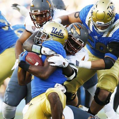 ASU's Tashon Smallwood (90) tackles UCLA Paul Perkins