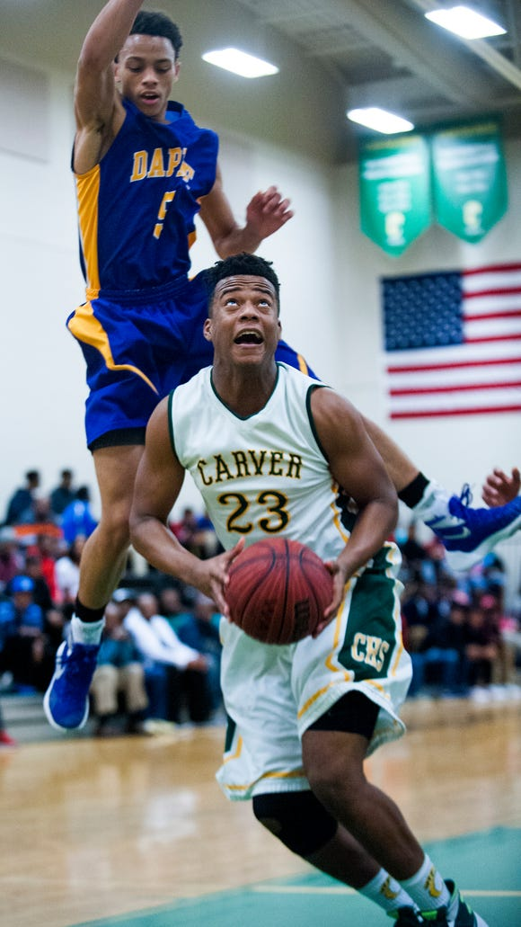 Carver's Xavious Turner (23) is defended by Daphne's