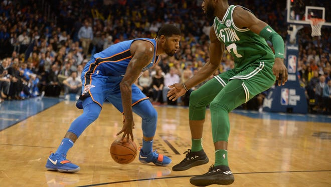 Nov 3, 2017; Oklahoma City, OK, USA;  Oklahoma City Thunder forward Paul George (13) controls the ball against Boston Celtics guard Jaylen Brown (7) during the second quarter at Chesapeake Energy Arena.