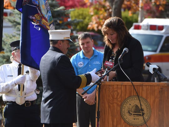 NY State Senator Sue Serino, right, presents the NY State Liberty Medal to City of Poughkeepsie Fire Chief Mark Johnson, left, during a ceremony commemorating Tim Gunther at Earline Patrice Park.