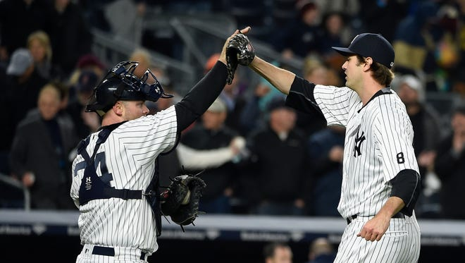 New York Yankees catcher Brian McCann (34) congratulates relief pitcher Andrew Miller after they defeated the Boston Red Sox in a baseball game, Friday, May 6, 2016, in New York.