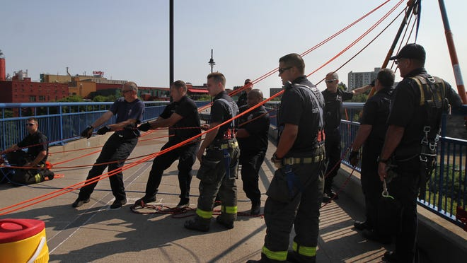 Rochester firefighters tighten the lines for a rope rescue practice in July. RFD is holding an open house Saturday.