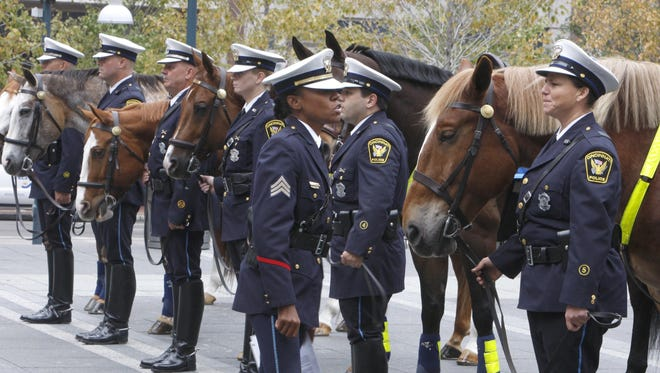 Sgt. Elena Moton, front, inspects a class of the Cincinnati Police Mounted Unit, including Police Officer Linda Borowicz, right, and her partner Bob, during graduation ceremonies on Fountain Square in downtown Cincinnati, Ohio Thursday Oct. 16, 2008.