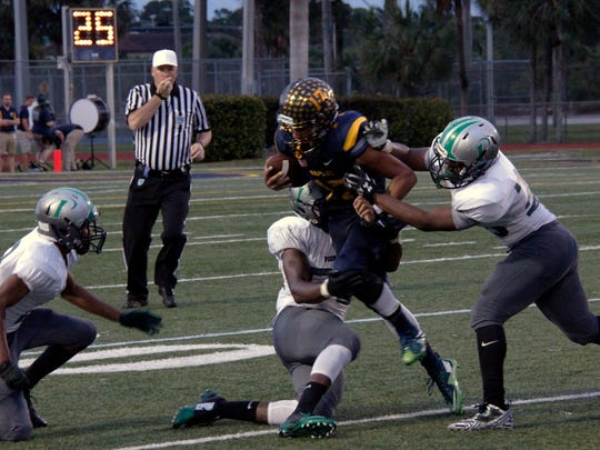 Naples QB Jordan Persad-Tirone is dragged down against North Miami for the spring classic at Staver Field on Friday, May 20, 2016. (J. Scott Butherus/Staff)