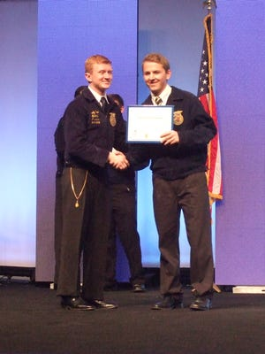 Brannick Sweetser, right, accepted his National American FFA Degree from National FFA President Andy Paul during an awards ceremony on Saturday at the National FFA Convention in Louisville, KY.