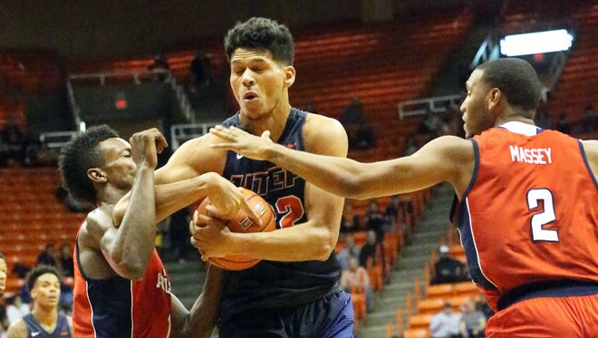 UTEP forward Paul Thomas holds on to the ball while driving to the basket against Florida Atlantic's Marcus Neely, left, and Justin Massey, 2, Saturday night. The Miners pulled away another victory with a 66-65 win in overtime.