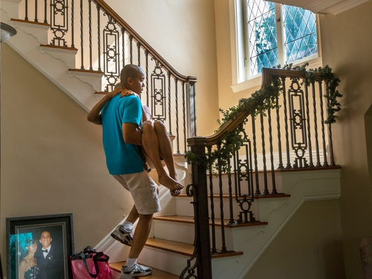 Christopher carries Pamela up the stairs. Holly left over from Christmas, is still on the banister.