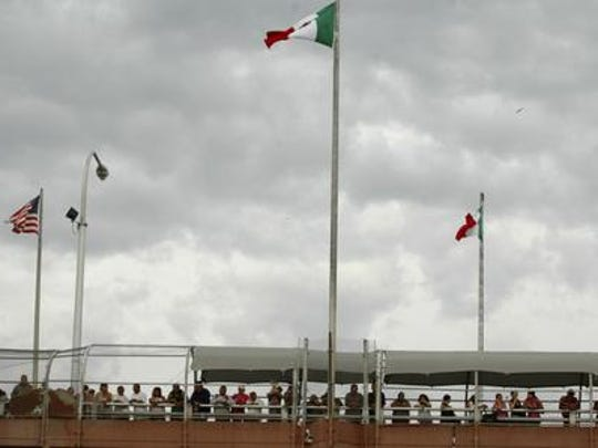 People standing on the Paso Del Norte border bridge watch the police activity below after 14 year-old Sergio Adrian Hernandez Huereca was killed below the bridge in the city of Ciudad Juarez, Mexico Monday June 7, 2010. Chihuahua State officials released a statement Tuesday June 8, demanding a full investigation into the death of the boy who was allegedly shot by a U.S. Border Patrol agent after a confrontation, according to Mexican authorities.(AP Photo)