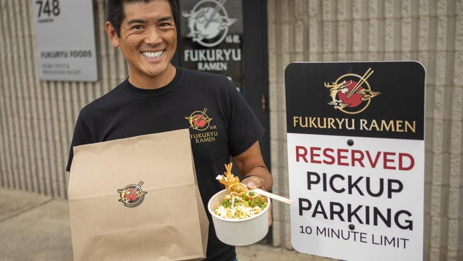 Fukuryu Ramen owner Jeff Tsao holds a shrimp tempura rice bowl from the restaurant's summer menu with a to-go bag outside the company's commissary kitchen on Harmon Avenue on the South Side.