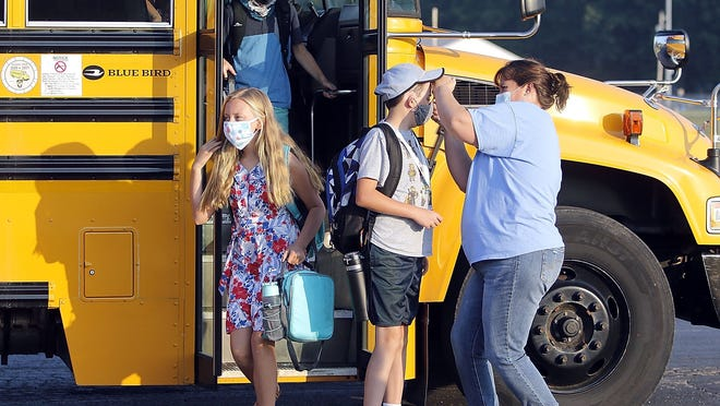 Rebecca Goodwin, fifth-grade teacher at Mapleton Elementary School, takes the temperature of students on their first day as they exit the bus and head toward the building Monday.