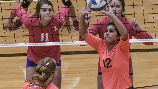 Garden City High School's Mya Cruz, right, sets the ball for teammate Abby Ellermann as Dodge City's Mataya Clark (11) and Kisa Unruh prepare to try to block the shot Thursday at GCHS during a volleyball triangular.