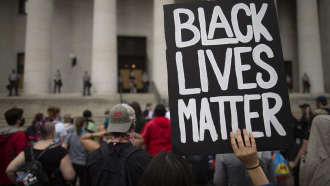 A protester holds up a Black Lives Matter sign during a protest for racial justice Downtown on Thursday, June 4, 2020.