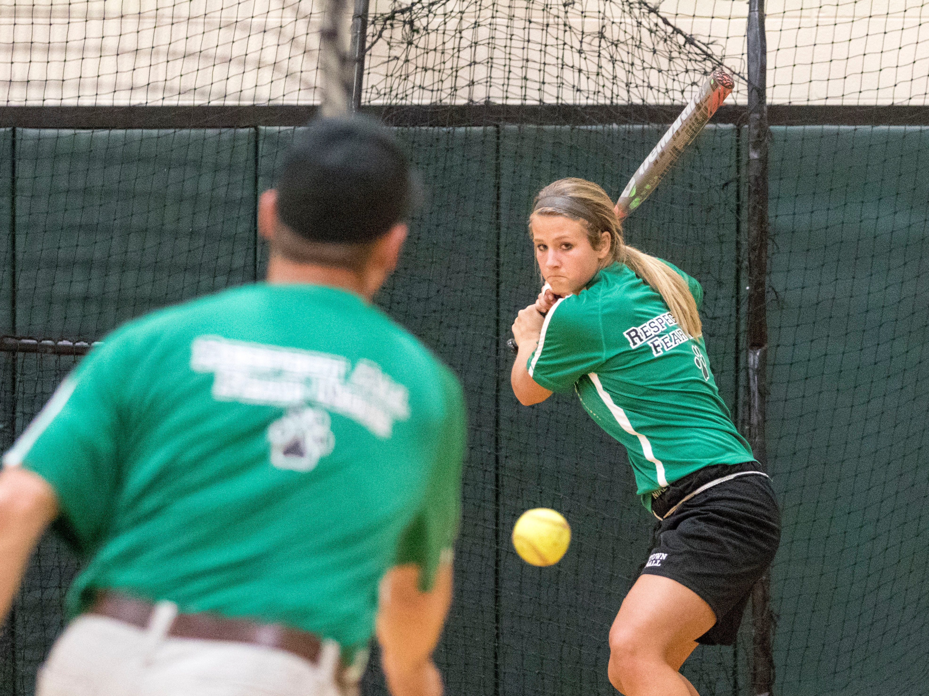 Yorktown softball coach Jeff Berger pitches a ball at senior Katy Johnson at practice on Thursday. Berger formerly was the coach at Cowan and hopes to help the senior-laden Tigers stay at a high level.