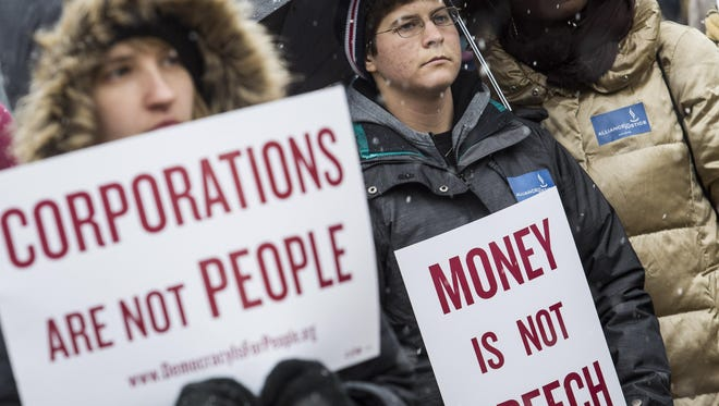 Attendees hold signs as they listen to speakers during a rally calling for an end to corporate money in politics and to mark the fifth anniversary of the Supreme Court's Citizens United decision, at Lafayette Square near the White House, Jan. 21, in Washington, DC.
