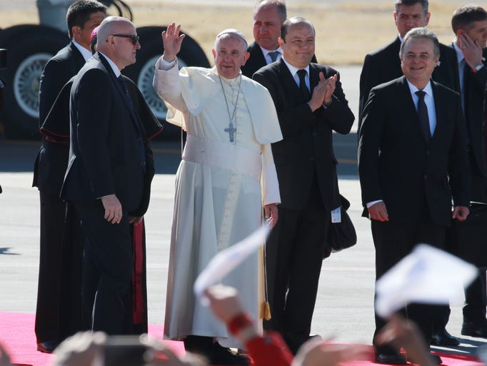 Pope Francis waves to the faithful after arriving at