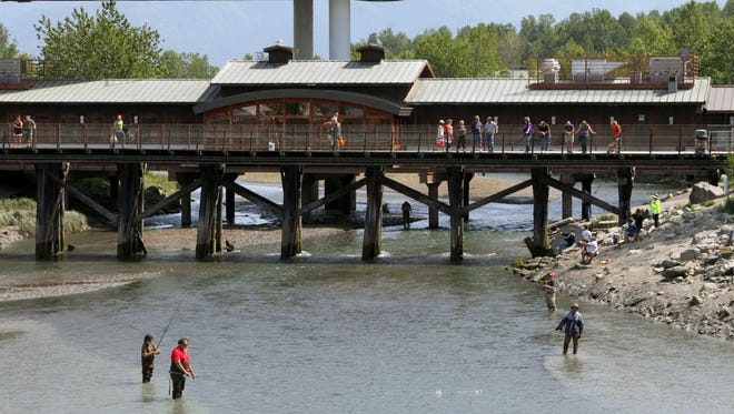 People watch fishermen angle for salmon on Ship Creek in downtown Anchorage, Alaska. Watching fishermen from pedestrian bridges is among some of the free activities for people to do while waiting to catch a flight home after an Alaska cruise.