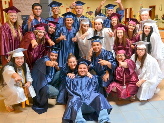Deming High School Principal Janean Garney (at bottom in center) poses with a few of the graduating seniors who visited schools in the district.