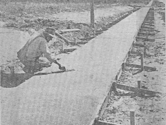 Waldo Treat puts finishing touches on the newly constructed sidewalk along South College Street in 1954.