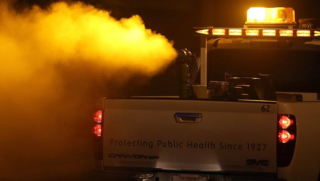 This file photo shows a truck driving through a neighborhood fogging with insecticide.