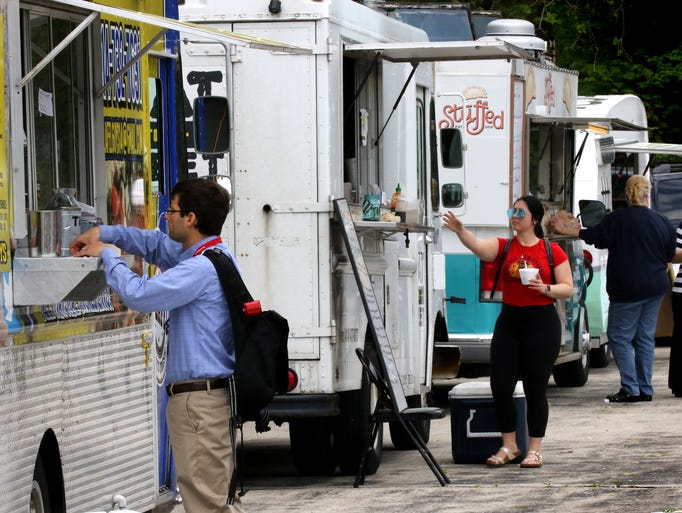 Diners stop a five food trucks for lunch items at the