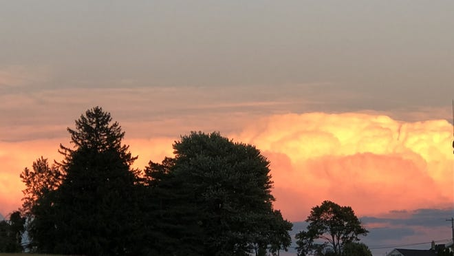Puffy white clouds serve as a palette for the setting sun in Seneca Castle, capping off a fine summer day.