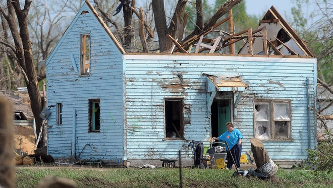 Mary Daugherty rummages for belongings from Sunday's tornado in Delmont on Tuesday, May 12, 2015.